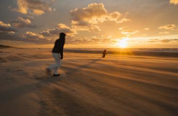 Dänemark, Jütland, Lokken, Mutter, die versucht ihr Kind auf stürmischem Strand bei Sonnenuntergang zu fangen
