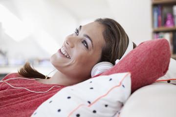 Porträt der Frau mit Kopfhörern auf einem Sofa liegend in ihrer Wohnung