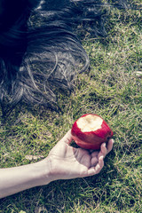Hand der Frau liegt auf dem Gras, roter Apfel angebissen