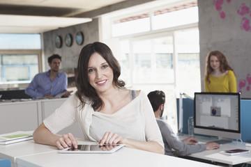 Lächelnde Frau mit Tablet-PC stehend in einem offenen Großraumbüro