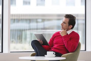 Business-Mann sitzt in Hotel-Lounge mit Tablet-Computer