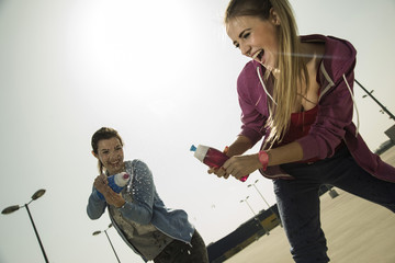 Zwei spielerische junge Frauen planschen mit Wasserflasche