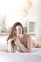 Lächelnde junge Frau in weißem BH und Höschen auf dem Bett liegend