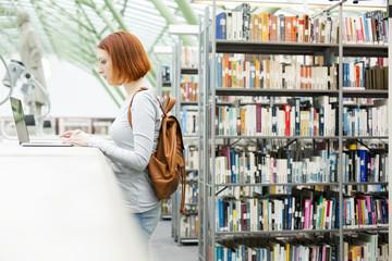 Student in einer Universitätsbibliothek mit Laptop