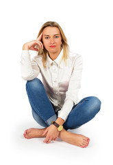 Portrait of attractive young blond woman sitting on floor and lo