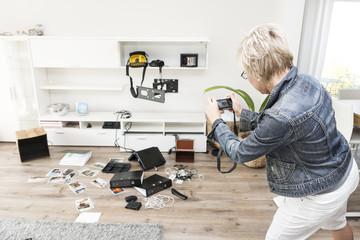 Frau fotografieren Chaos nach Einbruch in ihr Einfamilienhaus