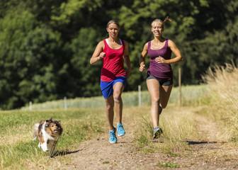 Zwei junge Frauen joggen mit Hund auf Feldweg