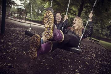 Zwei spielerische junge Frauen auf Schaukel