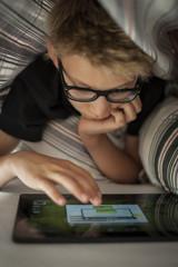 Zwei Jungen liegen auf dem Bett, mit iPad