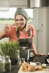 Portrait einer jungen Frau beim Kochen in der Küche zu Hause