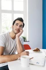 Nachdenklicher junger Mann sitzt am Frühstückstisch mit Zeitung