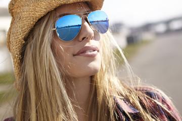 Junge Frau trägt Cowboy-Hut und Sonnenbrille