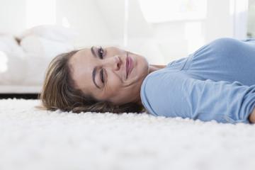 Frau liegt auf dem Teppich