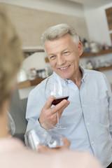 Portrait von reifem Mann mit Rotweinglas, mit Freunden zu Hause