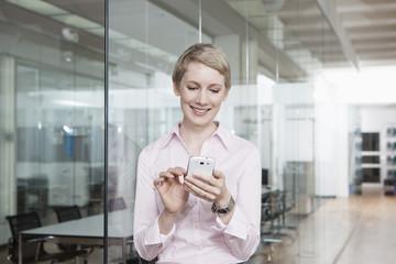 Geschäftsfrau im Büro, mit Smartphone