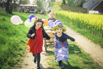 Drei Kinder in Bewegung mit Holzwagen und Luftballons