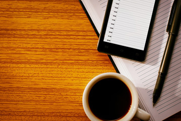 Cup of Coffee with Organizational Tools on Desk