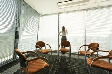 Geschäftsfrau im Büro, Blick durch Jalousien