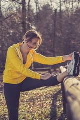 Frau macht Sport im Wald, Stretching auf einem Holzgeländer