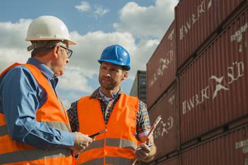 Zwei Männer mit Schutzhelmen und reflektierenden Westen reden am Containerhafen