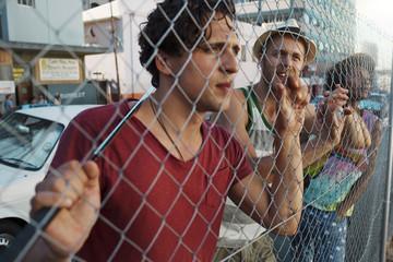 Freunde hinter Gitterzaun in der Stadt
