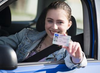 Teenager-Mädchen im Auto zeigt Führerschein