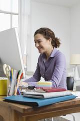 Frau zu Hause sitzend am Schreibtisch mit Computer