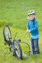 Kleiner Junge mit Fahrradreifen auf einer Wiese