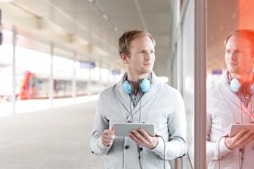 Junger Mann mit Tablet-PC und Kopfhörer