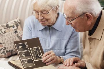 Senioren-Paar mit altem Foto-Album zu Hause