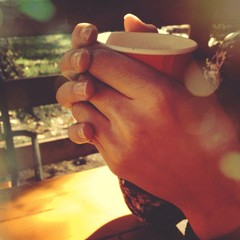 a girls hands holding a cup of instant coffee outdoors
