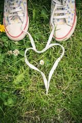 Schnürsenkel von zwei Turnschuhen, Herz auf Gras