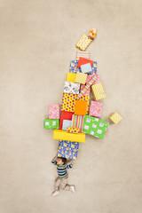 Junge balanciert Stapel von Geschenken