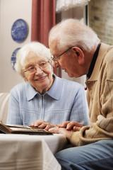 Älteres Paar schaut alte Fotos zu Hause an