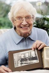 Ältere Frau, die altes Foto von sich selbst anschaut