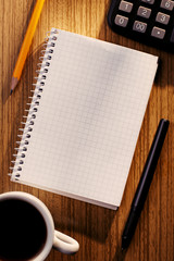 Notebook and Calculator on Desk with Cup of Coffee