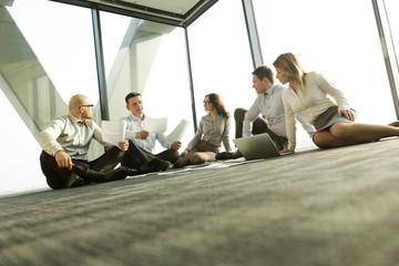 Geschäftsleute sitzen auf dem Boden und diskutieren Papiere