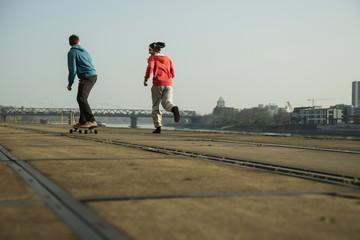 Junger Mann und Teenager Joggen und fahren Skateboard