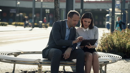 Business people working with tablet on bench in the city