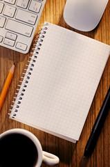 Open notebook with coffee alongside a keyboard