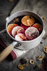 Auflauf mit Glühwein, Scheiben von Zitronen und Orangen und Gewürzen