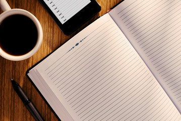 Open journal or diary with a mug of coffee