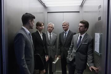 Gruppe von Geschäftsleuten diskutieren in Aufzug