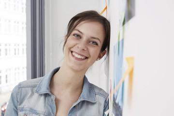 Lächelnde Frau lehnt an der Wand mit Haftnotizen