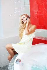 Woman in bathroom speaking on phone