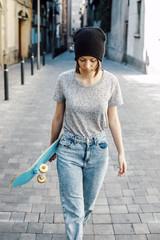 Junge Skateboarderin zu Fuß unterwegs