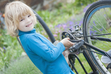 Lächelnder kleiner Junge, Reparatur Fahrrad