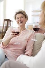 Zwei reife Frauen trinken Rotwein zu Hause