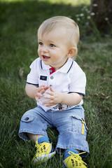 Deutschland, Oberhausen, blondes Baby sitzt auf dem Rasen im Park