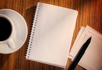 Notebook and Pen with Cup of Coffee on Desk
